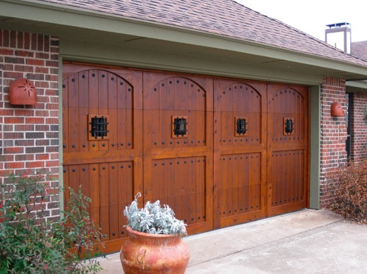 Premium Finish Wood Garage Door with Speakeasy Grills over Windows and Decorative Clavos